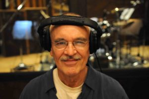John Clark wearing a headset in his french horn recording studio